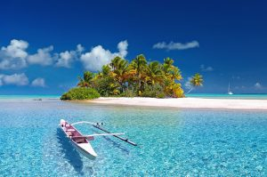 Small outrigger boat off a tiny sandy island in French Polynesia in incredible clear blue sea