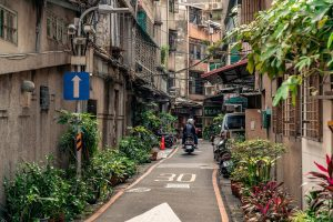 Small inner city road in Taipei with a moped riding it