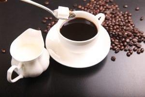black coffee having a lump of sugar added