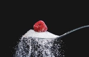 a raspberry atop a overflowing spoon of sugar