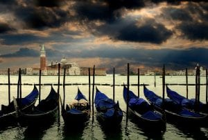 Gondolas moored up under a stormy looking sky