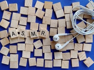 scrabble tiles spelling out ASMR with a set of ear pods in the shot