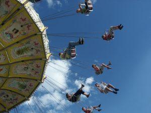 people having fun on a carousel fairground rise