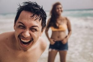 young couple laughing together on the beach