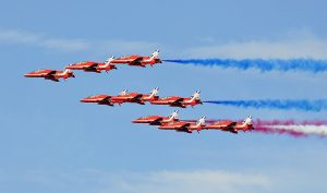 The Red Arrows flying in Formation with blue smoke trails