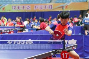 A large hall full of people playing table tennis