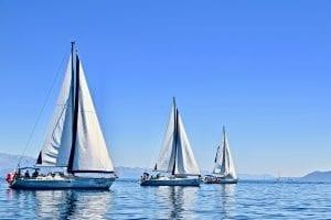 three yachts sailing on calm waters