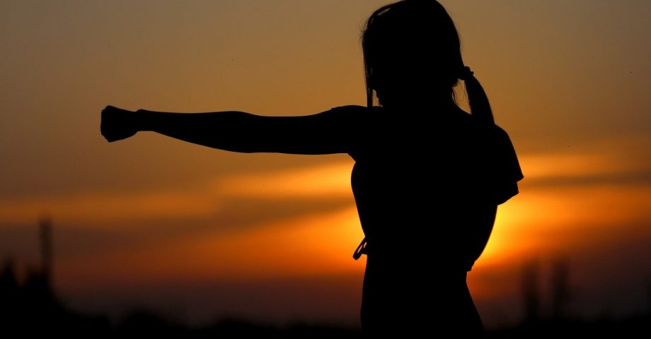 woman practicing karate with a sunset background