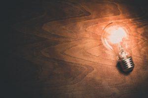 a light bulb shining against a backdrop of wood