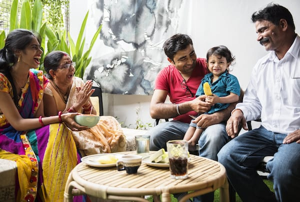 Indian family laughing and passing food at the table