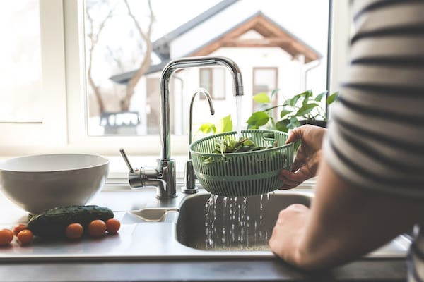 Woman washing lettuce over sink
