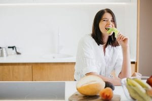Young happy woman eating green lettuce leaf and smiling on background of fresh fruits and vegetables in modern white kitchen. Healthy food concept. Home cooking