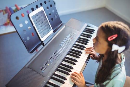 Elementary girl practicing digital piano at school