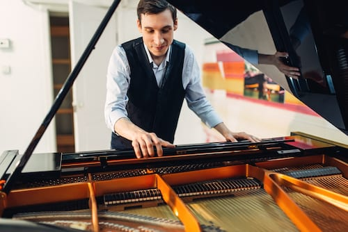Male pianist sets the grand piano before performance.