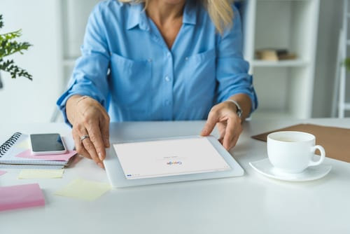 Businesswoman using digital tablet with Google website
