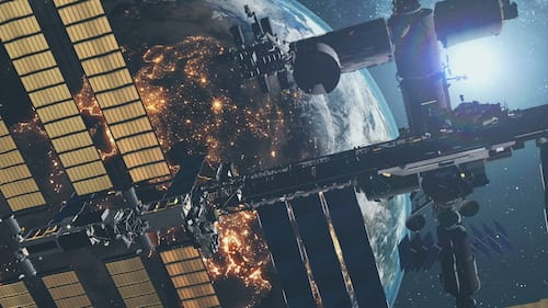 International Space Station with solar charging panels flies in outer space against starlight.