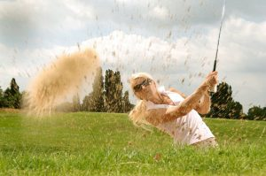 woman playing golf, hitting out of the sand
